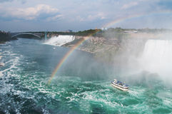 Härlig regnbåge som bildar nära det turist- fartyget på Niagara Falls Royaltyfria Foton