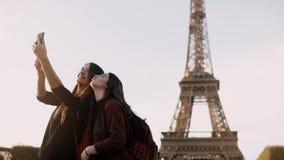 Härlig resande kvinnlig som två tar foto på smartphonen nära Eiffeltorn i Paris, Frankrike i solig dag lager videofilmer