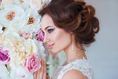 Härlig romantisk ung kvinna i den eleganta klänningen som poserar på en bakgrund av blommor Inspiration av våren och sommar Royaltyfri Foto