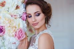 Härlig romantisk ung kvinna i den eleganta klänningen som poserar på en bakgrund av blommor Inspiration av våren och sommar Arkivbilder