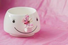 Härlig rosa bakgrund med den vita koppen och fjärilen arkivfoto