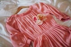 Härlig rosa färgklänning på sängen Arkivfoton