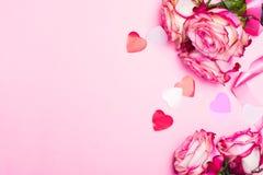 Härlig rosa färgros, dekorativa konfettihjärtor och rosa band på rosa valentindagbakgrund Arkivfoton