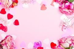 Härlig rosa färgros, dekorativa konfettihjärtor och rosa band på rosa valentindagbakgrund Arkivfoto