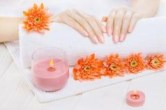 Härlig rosa manikyr med den orange krysantemumet och handduk på den vita trätabellen Spa Arkivbilder
