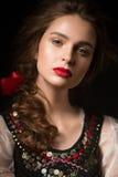 Härlig rysk flicka i nationell klänning med en flätad trådfrisyr och röda kanter Härlig le flicka fotografering för bildbyråer
