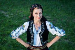 Härlig sångare som poserar i traditionell dräkt, romanian f Arkivfoton