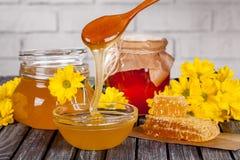 Härlig sammansättning av honungprodukter, honung, honungskakor, pergaen och sommarblommor på en trätabell arkivfoton
