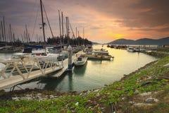 Härlig sammansättningssikt av den malaysiska hamnen med en yatch under solnedgång Royaltyfria Bilder
