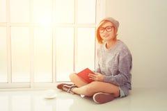 Härlig sammanträdeläsebok för ung kvinna nära fönsterblick på c arkivfoton