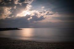 Härlig sandig scenisk strand i solnedgång, med den steniga vågbrytaren i lång exponering i basque land, Frankrike, idérik bakgrun royaltyfri bild