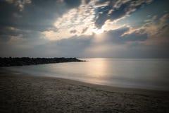 Härlig sandig scenisk strand i solnedgång, med den steniga vågbrytaren i lång exponering i basque land, Frankrike, idérik bakgrun royaltyfri foto