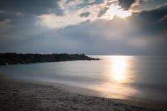 Härlig sandig scenisk strand i solnedgång, med den steniga vågbrytaren i lång exponering i basque land, Frankrike, idérik bakgrun fotografering för bildbyråer