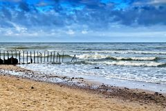 Härlig sandig strand och den gamla rostiga vågbrytaren royaltyfri foto