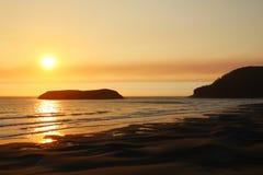 Härlig sandig strand på Stilla havet under en ljus solnedgång royaltyfri bild