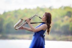Härlig saxofon för ljud för klänning för afton för blått för kvinnakläder över mou Arkivfoton