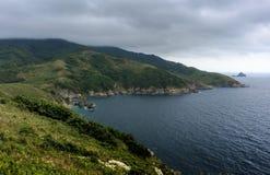Härlig seascape - gröna kullar, hav, ö på horisontunden royaltyfria foton