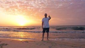 Härlig seascape med den gladlynta mitt åldrades upp manvisningtummen på soluppgång arkivfilmer