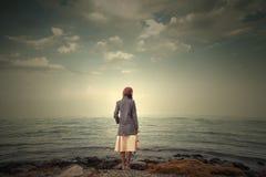 härlig seascape med den retro flickan på kusten Fotografering för Bildbyråer