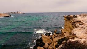Härlig seascape med den steniga klippan, havet och molnig himmel på horisont lager videofilmer