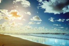 Härlig seascape med havsvågor, blå himmel, vita stackmolnmoln och sand sätter på land Tropiskt landskap för sommarsemester Arkivfoto