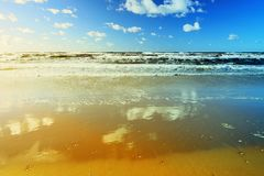 Härlig seascape med havsvågor, blå himmel, vita stackmolnmoln och sand sätter på land Tropiskt landskap för sommarsemester Fotografering för Bildbyråer