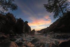 Härlig seascape med vågen och att vagga på solnedgången royaltyfria foton