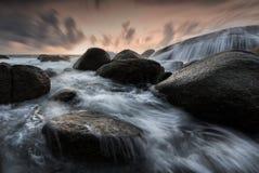 Härlig seascape med vågen och att vagga på solnedgången royaltyfri fotografi