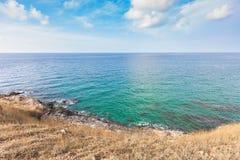 Härlig seascape med vaggar och ängen i molnig blå himmel arkivfoton