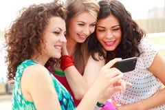 härlig seende smartphone tre kvinnor Arkivfoto