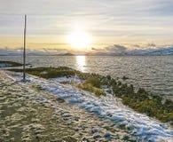 Härlig September solnedgång på de snöig kusterna av en lugna nordlig fjord i Norge fotografering för bildbyråer