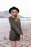 Härlig sexig blond flicka som poserar i bergen på en sprucken jordning i en svart hatt med ljust smink Royaltyfri Foto
