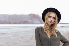 Härlig sexig blond flicka som poserar i bergen på en sprucken jordning i en svart hatt med ljust smink Arkivfoto