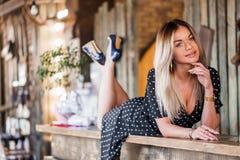 Härlig sexig blond kvinna som ligger på stången och le Mottagande kopieringsutrymme royaltyfria bilder