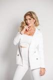 Härlig sexig blondin i en vit dräkt som poserar på vit bakgrund Royaltyfri Fotografi