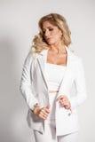 Härlig sexig blondin i en vit dräkt som poserar på vit bakgrund Royaltyfria Foton