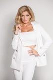 Härlig sexig blondin i en vit dräkt som poserar på vit bakgrund Royaltyfria Bilder