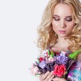 Härlig sexig blygsam sötsakanbudflicka med lockigt anseende för blont hår på vit bakgrund med en bukett av blommor av lavendel Royaltyfri Bild