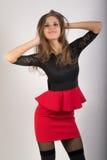 Härlig sexig brunettflicka i röd kort kjol Arkivfoton