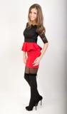 Härlig sexig brunettflicka i röd kort kjol Fotografering för Bildbyråer