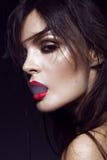 Härlig sexig brunettflicka med ljus makeup, röda kanter, rök från mun Härlig le flicka Arkivbilder