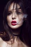 Härlig sexig brunettflicka med ljus makeup, röda kanter, rök från mun Härlig le flicka Royaltyfri Foto