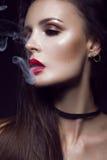 Härlig sexig brunettflicka med ljus makeup, röda kanter, rök från mun Härlig le flicka Royaltyfri Fotografi