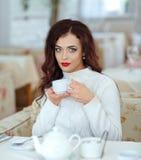 Härlig sexig brunettflicka med röd läppstift i en vit sweate Royaltyfria Bilder