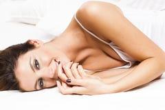 Härlig sexig brunettkvinna på sängen Arkivbild