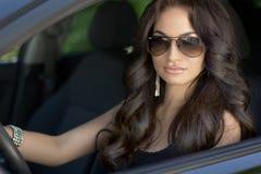 Härlig sexig brunettkvinnamodell med solglasögon som sitter i a Arkivbild