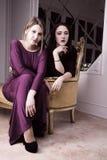Härlig sexig elegant flicka två i aftonklänningar royaltyfri fotografi