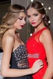 Härlig sexig elegant flicka två i röda och svarta aftonklänningar med den ljusa frisyren för aftonsminkafton och fästingar på han fotografering för bildbyråer