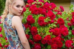 Härlig sexig försiktig elegant kvinna med vitt hår med härligt hår i sundress som står i trädgården nära en stor buske av rött arkivbild