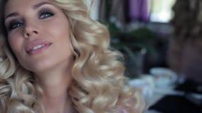 Härlig sexig flicka med lockigt hår i en skönhetsalong lager videofilmer
